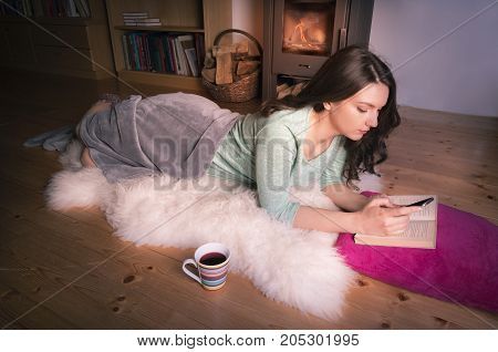 Young brunette girl relaxing in front of the fireplace lying on a white fur on the floor while using a smart phone having an open book and a cup of tee near her.