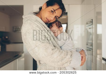 Young Woman Carrying Her Newborn Baby Boy