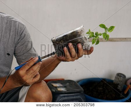 Man use the tool drilling plastic glass to keep the water running for plant