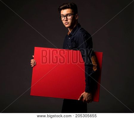 Young  confident man portrait of a businessman showing presentation, pointing paper placard black background. Ideal for banners, registration forms, presentation, landings, presenting concept.