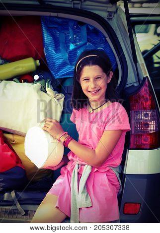 Cute Little Girl Loads Her Purse In The Car Trunk