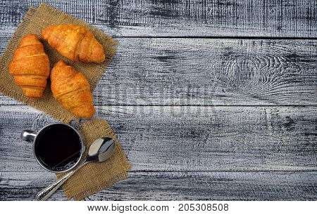 Fresh croissants and hot coffee on an old wooden table. Top view.
