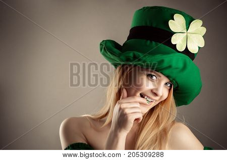 seductive blond girl in image leprechaun isolated on gray background
