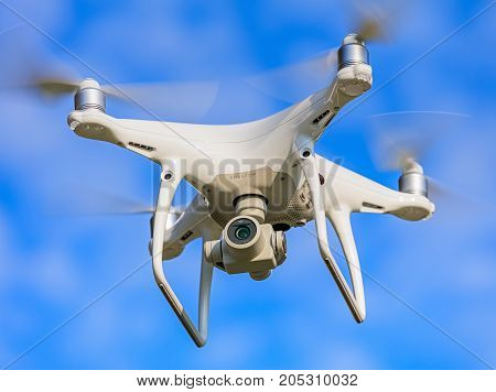 Wallisellen, Switzerland - 23 September, 2017: a Phantom 4 Pro drone flying in the blue sky, selective focus on front of the drone. Phantom 4 Pro is a consumer drone designed and manufactured by the DJI company.