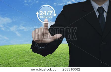 Businessman pressing button 24 hours service icon over green grass field with blue sky Full time service concept