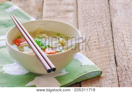 Homemade minced pork wonton soup in white bowl on napkin put on wood table with copy space. Delicious wonton in clear soup for breakfast or lunch or dinner. Wonton or dumpling is always popular Chinese food. Wonton soup ready to served.