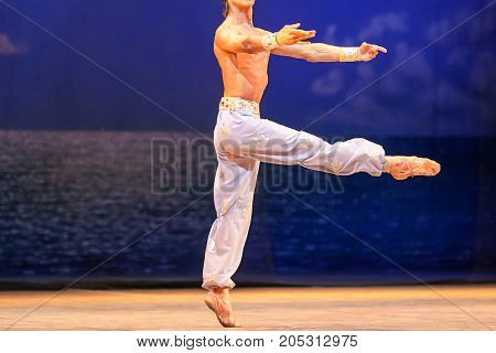 dancing, rehearsal, amusement concept. on the stage of theater man wearing light blue pants and pointe shoes performing the dance solo of well known great ballet corsar