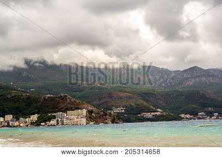 Clouds over the beaches of Montenegro. Mountains and the sea in non-sharp weather. Budva. Becici.