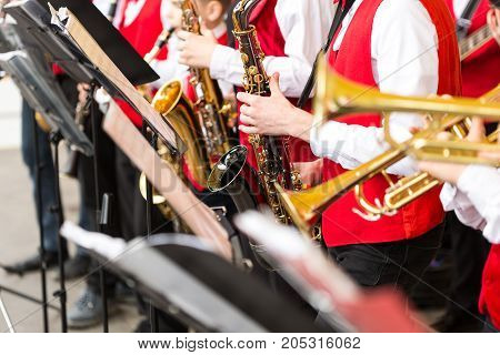 orchestra musical instruments, brass band concept - ensemble of musicians playing on trumpet and saxophone in concert costumes, closeup music stands and male hands with equipment, selective focus