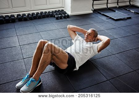 Focused mature man in sportswear lying on the floor doing sit ups alone while working out in a gym