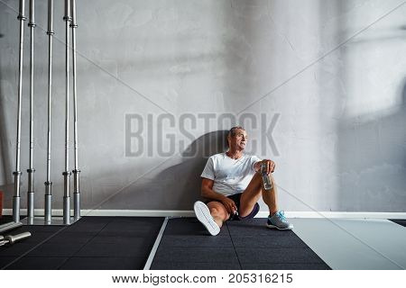 Senior Man Drinking Water And Resting After A Gym Workout
