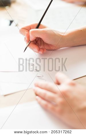 penmanship, hobby, graphic design concept. well groomed hands of young caucasian woman who writing letters of russian alphabeth in harmonious and aesthetic manner with ink and brush