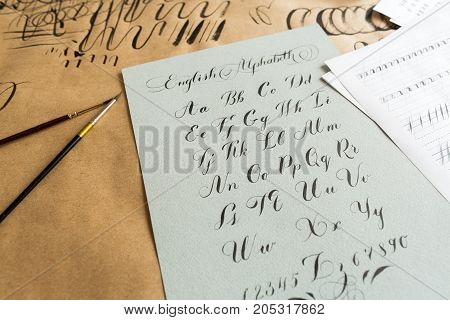lettering, technique, drawing concept. english alphabeth written in italic style with elegant and smooth lines maded with help of thin tip of the brush and black ink