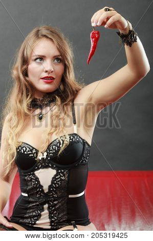 Sensual seductive attractive woman wearing lingerie holding and looking at chilli pepper. Erotic fashion concept
