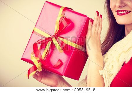 Cheerful woman holding present big red gift box. Christmas season celebration concept. Toned image