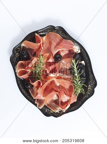 Serrano with rosemary and olives on a black plate .