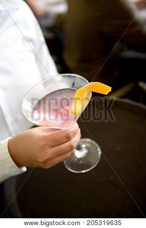 fresh tasty cocktail and orange skin on hand