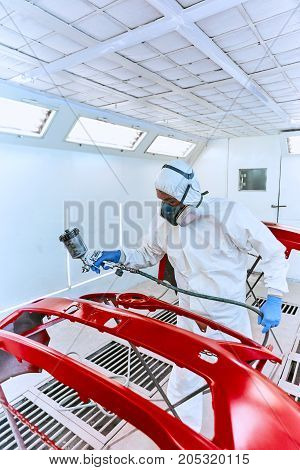 Painting the car's bumper red on the service.