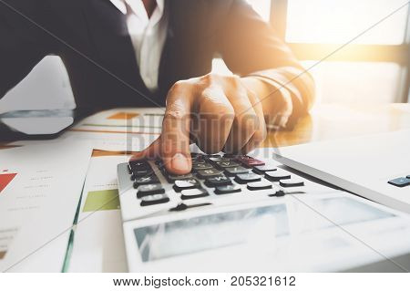 Business man using calculator doing stock valuation. Accountant concept.
