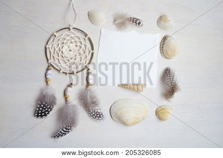 Seashells frame on wooden background with place for text. Card for a beach party invitation advertising. Dreamcatcher.