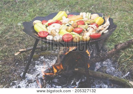 Different kind of vegetables grilling on charcoal grill. Assorted grilled tomato, potato,  mushrooms, zucchini, bell pepper on a summer barbecue, BBQ concept. Picnic.