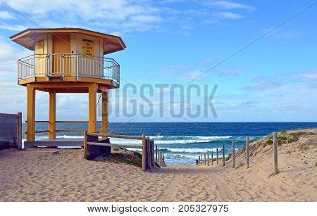 Yellow lifesavers hut and path leading onto Wanda Beach, Cronulla, New South Wales, Australia.