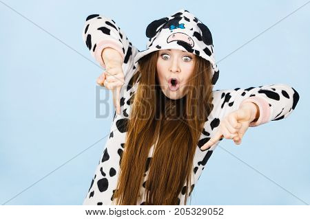 Happy teenage girl in funny nightclothes pajamas cartoon style pointing down with positive surprised face expression studio shot on blue. Advertisement concept