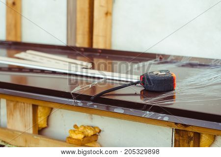 the construction tape measure rests on the windowsill outside the house