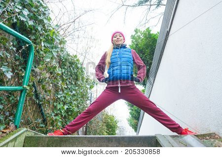 Outdoor sport exercises sporty outfit ideas. Woman wearing warm sportswear training exercising stretching legs outside during autumn.