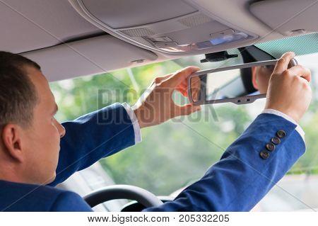 driver businessman adjusts rear view mirror in car interior