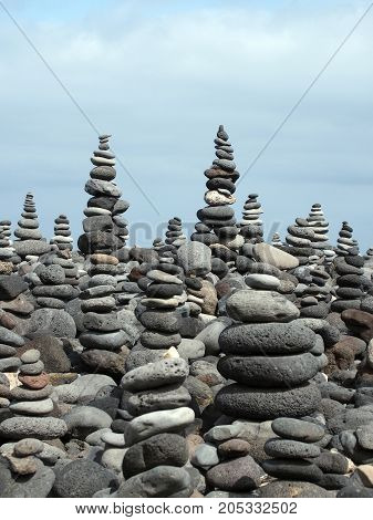 rock art piles and towers of grey stones and pebbles on a beach with blue sky