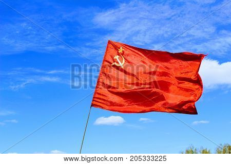 Waving flag of the USSR against the blue sky.