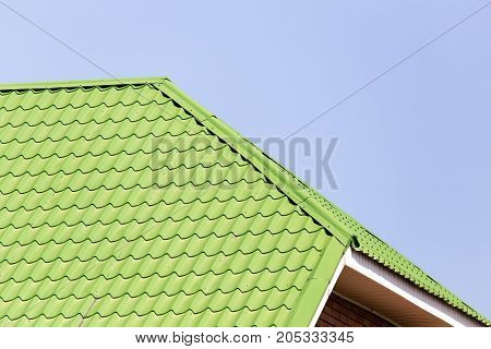 green roof on the house against the blue sky .