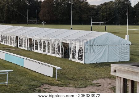 Big white banquet tent with windows near the green fields and tree.