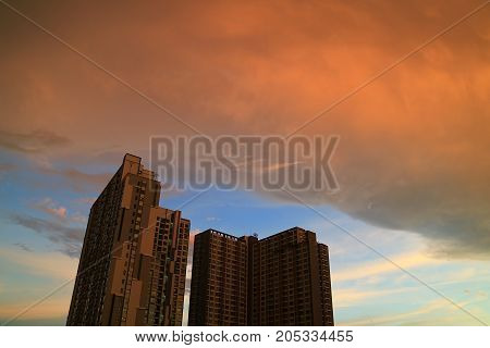 The rain clouds with sunset afterglow reflections scrolling on the building in Bangkok, Thailand