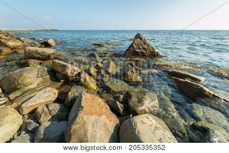 Sea waves lash line impact rock on the beach. Sunny backgrounds wallpaper. Black Sea