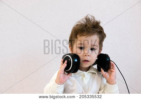 Pop music. Happy smiling newborn baby listens to music in headphones on gray background. Cheerful children's portrait. Little Adorable baby boy with big headphones. funny seri. ous emotions.