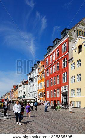 Copenhagen Denmark - August 24 2017: Street view of the colorful building in Nyhavn in Cophenhagen with people walking the street in front.