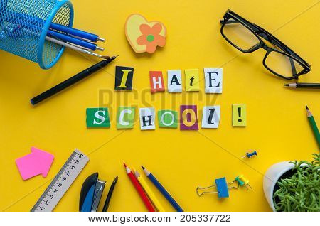 School supplies on yellow background with text I HATE SCHOOL.