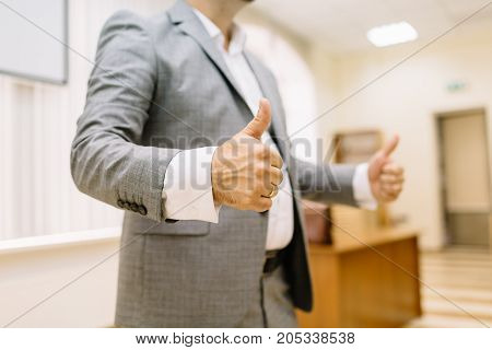 A successful business man showing thumbs up sign on the office background. Close-up of a confident entrepreneur in a suit.