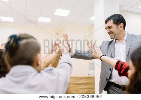 A large group of office staff giving each other a high-five on a blurred room background. Businessman supporting his workers.