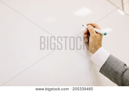 Close-up of a lecturer writing on a multimedia projector on a light background. Mature teacher writing on a white desk. Copy space.