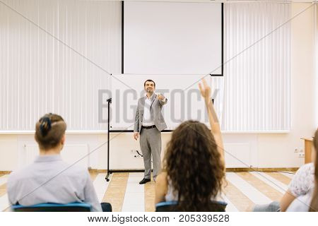 A cheerful mature lecturer on a meeting with students on a classroom background. Educational conference. Copy space.