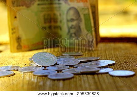 Indian currency coin and note on wooden texture ,