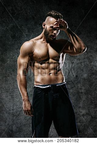 Tired athletic man wiping sweat his hand. Photo of man with perfect body after training. Strength and motivation