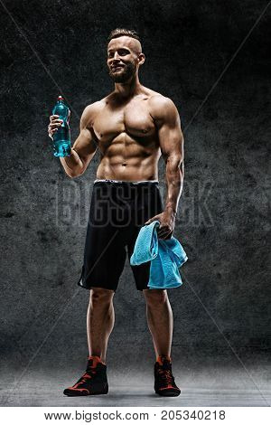 Sporty man having a break. Photo of muscular man with water and towel in his hands on dark background. Health concept.