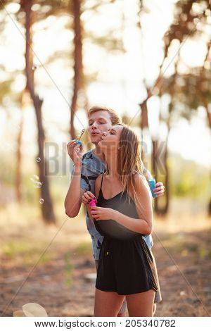 Pretty boy with his girlfriend have great time together with bubble blower - outside in street.