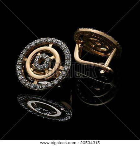 macro of golden earrings on black background