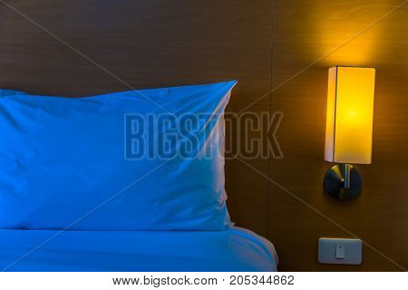 bedside lamp with its warm light turned on next to white bed and pillow at night with space for text or copy space good for home at night or lonliness concept