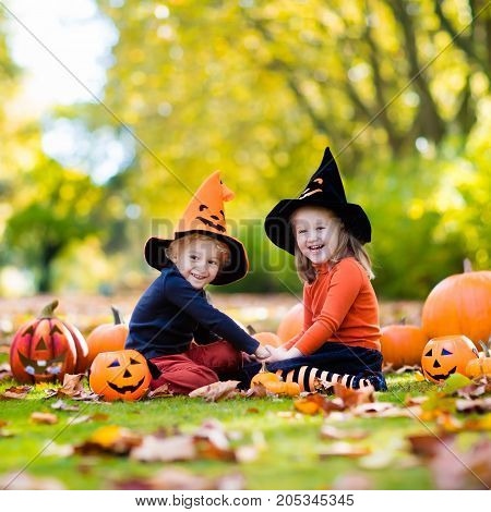 Kids With Pumpkins In Halloween Costumes